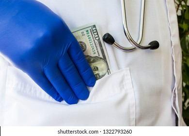 Doctor hides or lays down hundred dollar bill in pocket of white doctoral coat. Concept photo bribes, corruption in medicine, payment of medical care in private practice or public medicine, wages