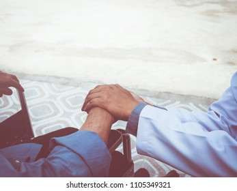 Doctor hold hand patient on wheelchair outdoor.