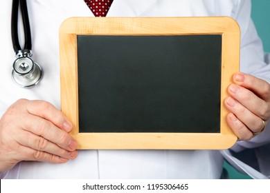Doctor holding blank chalkboard in Detail