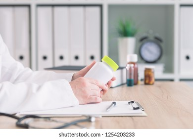Doctor holding bottle of dietary supplement in medical office