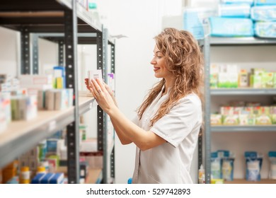 Doctor holding a box of pills in hands inside the warehouse. Healthcare business