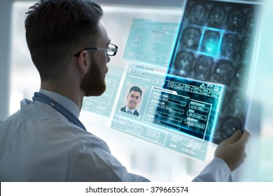 Doctor holding brain mri and examining it using virtual future technology