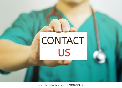 Doctor holding a  business card with capital lettering CONTACT US in hand.Medical and healthcare  concept, medicals support and service, Selective focus.vintage tone.
