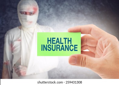 Doctor holding an business card with Health Insurance title, Injured unwell man in bandages in the background.