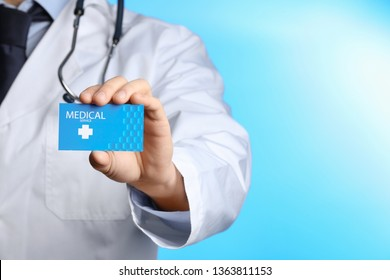 Doctor holding business card on color background, closeup with space for text. Medical service