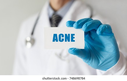 Doctor holding a card with text ACNE, medical concept