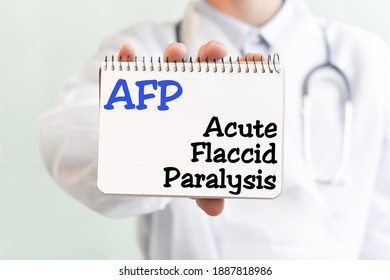 Doctor holding a card with text AFP Acute Flaccid Paralysis, medical concept. The text is written in blue letters in a medical journal.