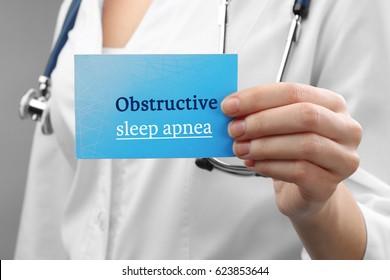Doctor holding card with text OBSTRUCTIVE SLEEP APNEA, closeup