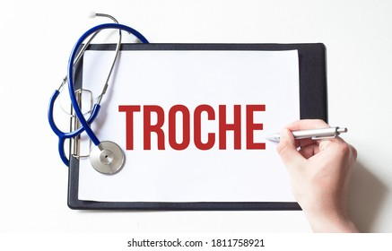Doctor holding a card with text TROCHE, medical concept