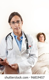 Doctor holding a cardboard with exams with a senior patient in the background