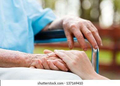 Doctor holding elderly patient 's hand in a wheelchair.