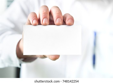 Doctor holding empty white business card. Blank copy space for content.