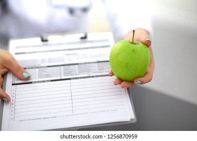 Doctor holding fresh green apples, closeup shot