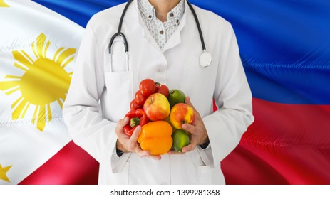 Doctor is holding fruits and vegetables in hands with Philippines flag background. National healthcare concept, medical theme.