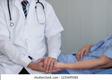 Doctor holding hand of elderly woman  patient for reasurring and support