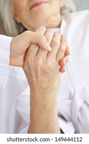 Doctor holding hand of senior woman patient for comfort in a hospital