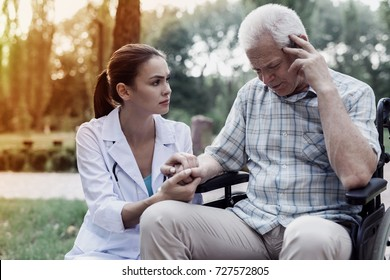 Doctor holding the hand of a sick old man on a wheelchair in a summer park
