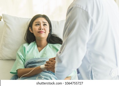 Doctor holding hands and encouraging depressed female patient to fight with cancer on the bed in the hospital. Selective focus on hands.
