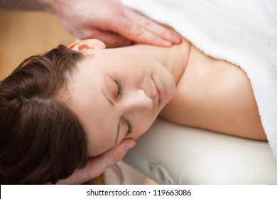 Doctor holding the head of a woman while massaging her neck in a room