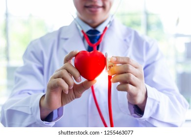 Doctor is holding heart and using stethoscope for examining fake heart at hospital room. Doctor who wants telling everyone take care their health by exercise for protecting heart attack, arrhythmia.