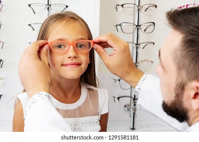 Doctor holding orange glasses on the little girl in the optical store