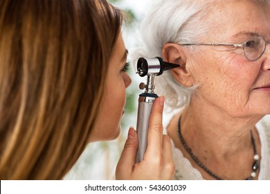 Doctor holding otoscope and examining ear of senior woman in ambulance