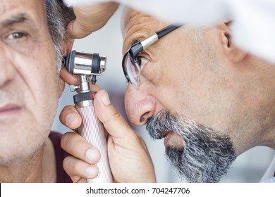 Doctor holding otoscope and examining ear of senior man