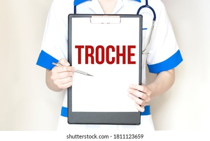 Doctor holding a paper plate with text TROCHE, medical concept