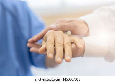 Doctor holding patient's hands of female patient giving support On Bed In Hospital. medical health care, helping hand.