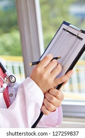Doctor holding pen and clipboard with checklist in a hospital