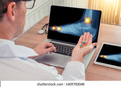 Doctor holding pills with x-ray of a foot with pain on the toes and ankle on a laptop. Digital tablet on the desk