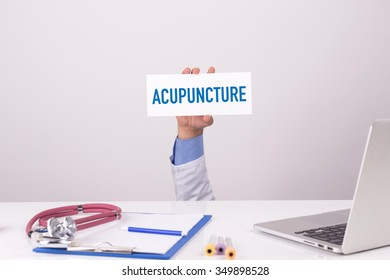 Doctor Holding Placard written ACUPUNCTURE