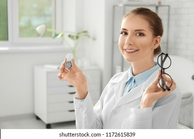 Doctor holding plastic container with contact lenses and glasses in clinic