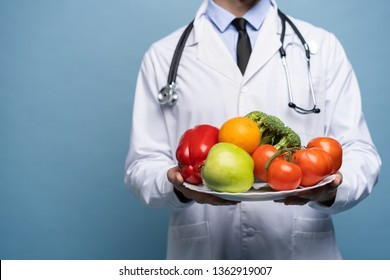 doctor holding plate of fresh vegetables isolated on light blue, healthy eating concept
