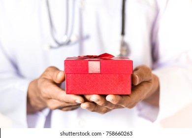 Doctor holding the red gift box in his hand