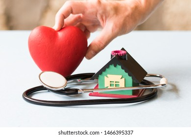 Doctor holding red heart, stethoscope and clinic symbol. Healthcare concept.