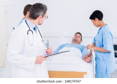 Doctor holding reports with patient and surgeon in background at the hospital