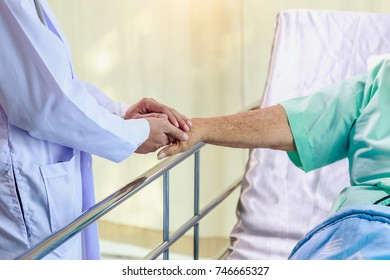 Doctor holding senior patient's hands in bed at hospital room, health care and people concept
