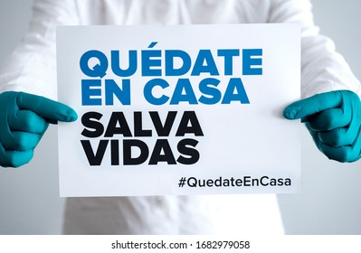 """Doctor holding sign """"Stay Home Save Lifes"""" in Spanish, global message for the coronavirus crisis. Quarantine message across the globe to fight COVID-19 pandemic."""