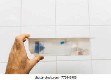 Doctor holding sterile disposable syringe in clean tile wall medical environment used for scanner irm er or other medical control