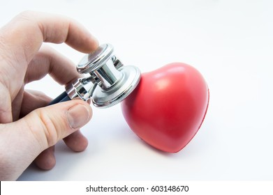 Doctor holding stethoscope in his hand, examines heart shape for presence of diseases of cardiovascular system. Photo for use in cardiology, cardiac surgery, diagnosis and treatment of heart disease