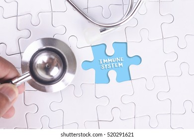Doctor holding a Stethoscope on missing puzzle WITH IMMUNE SYSTEM WORD