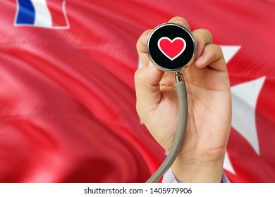 Doctor holding stethoscope with red love heart. National Wallis And Futuna flag background. Healthcare system concept, medical theme.