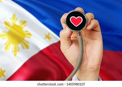 Doctor holding stethoscope with red love heart. National Philippines flag background. Healthcare system concept, medical theme.