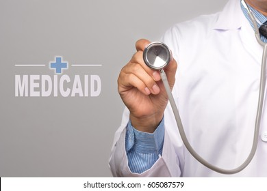 """Doctor holding a stethoscope and word """"MEDICAID"""" as medical concept."""