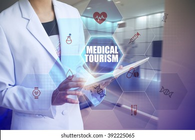 Doctor holding tablet with MEDICAL TOURISM text and working with modern computer interface , E-Health concept , business concept , business idea