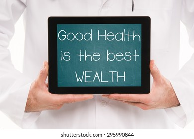 Doctor holding a tablet pc with GOOD HEALTH is the BEST WEALTH text on a green chalkboard screen.