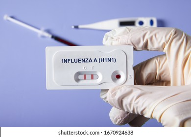 Doctor holding a test kit for viral diseases H1N1 flu and COVID-19 2019-nCoV. Lab card kit tested NEGATIVE for viral novel coronavirus sars-cov-2 virus and POSITIVE for H1N1