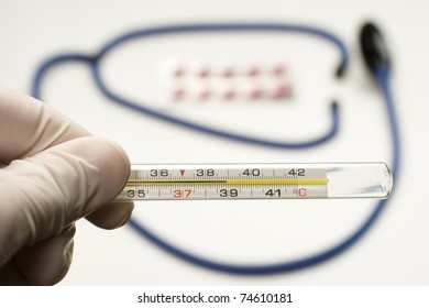 doctor is holding thermometer showing high temperature with stethoscope and tablets on background