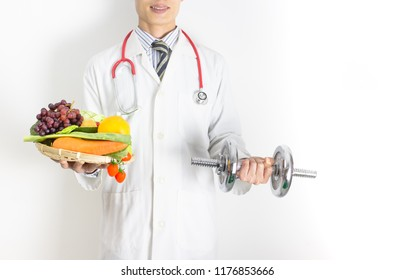 Doctor holding tray with heart healthy foods and dumbbell ,check a healthy eating ,workout and fitness dieting ,fitness and weight loss concept